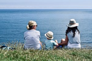 grandmother, mother, and child sitting by lakeshore time to update estate plan