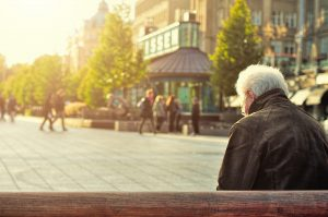 older man sitting on bench thinking about retirement accounts and beneficiaries
