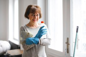 woman cleaning home and getting ready to contact lawyer about estate plan