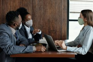 business meeting during covid19 with worker and customer wearing masks